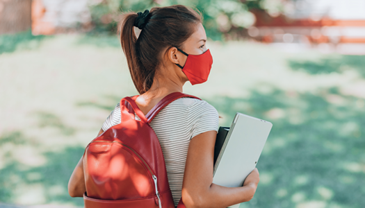 white female wearing red backpack and red face mask