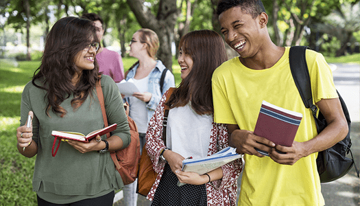 Group of smiling students walking across the college campus carrying books.