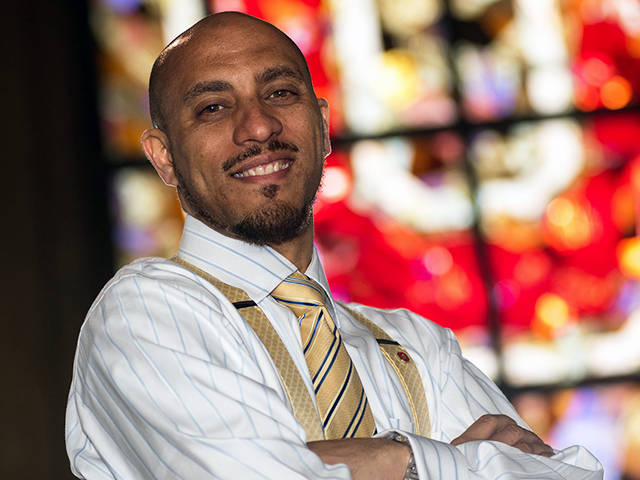 Hasan Kwame Jeffries, Ph.D. in shirt and tie posing in front of a stained glass window