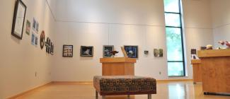 inside of the art gallery space with display of artwork hanging on the walls