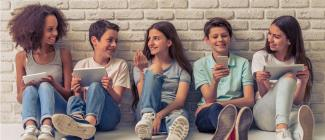 Five pre to early teenagers interacting while sitting against a white brick wall