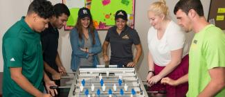 students playing foose ball game in student lounge