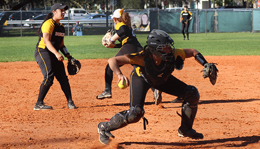 Three women softball players in action.