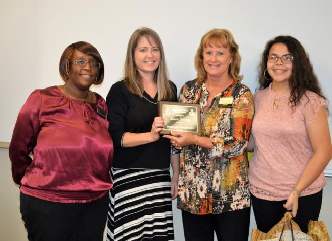 four females, left to right, two center women holding a Take Stock in Children Mentor of the Year plaque